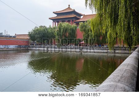 Beijing, China - Oct 30, 2016: Quezuo Gate across the Tongzi River moat. Outside the Forbidden City (Gu Gong, Palace Museum), along Donghuamen Road. A hazy day.