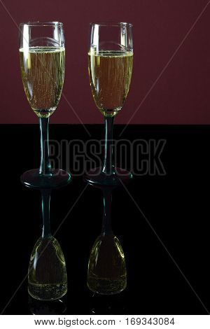Two glasses of champagne on black table with reflection.