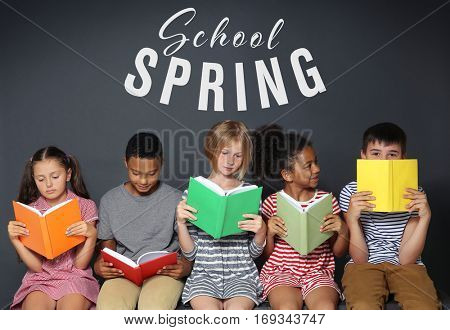 Text SCHOOL SPRING and children with books on dark background. Additional education concept