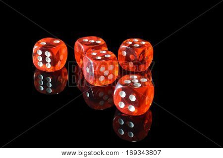 Five transparent red dice on black surface with reflection.