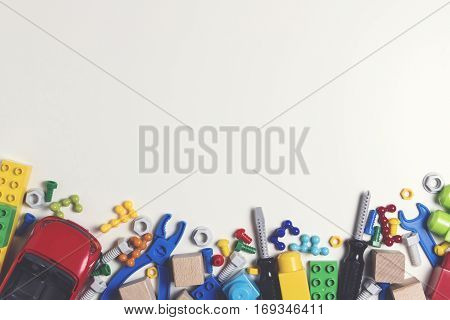 Colorful kids toys frame. Plastic toy construction tools, bolts, nuts, car, blocks, cubes on white background as frame with copy space for text. Flat lay. Top view. Toned picture
