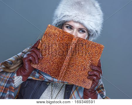 Portrait Of Woman Hiding Behind Book And Looking Copy Space
