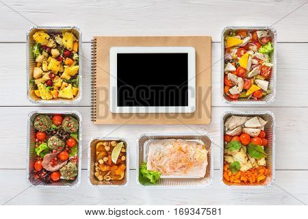 Healthy restaurant food internet online order background. Eating right. Fresh diet daily meals delivery. Nutrition with vegetables, meat and fruits in foil box. Top view, flat lay on wood, copy space