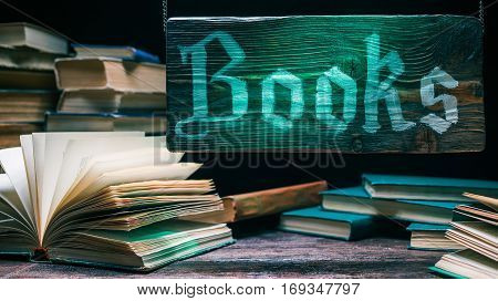 Various ancient books in traditional bookshop. Wooden green-lighted sign