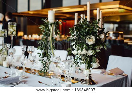 Table covered, served for a banquet in a restaurant with invitation on the background with flowers candles and candlesticks