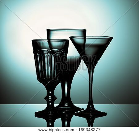 Three Various Empty Wine Glasses for Wine and Martini with Reflection on Glass and Shadow Backlight. Turquoise Toned