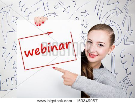Young woman holding whiteboard with writing word: webinar. Technology, internet, business and marketing