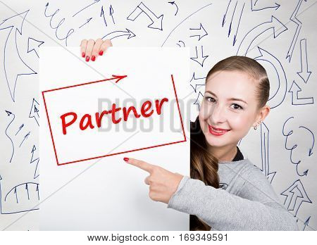 Young woman holding whiteboard with writing word: partner. Technology, internet, business and marketing