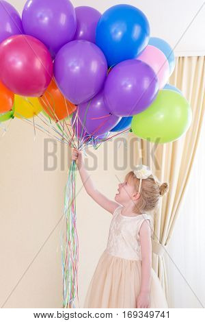 Little girl in dress with balloons in hand