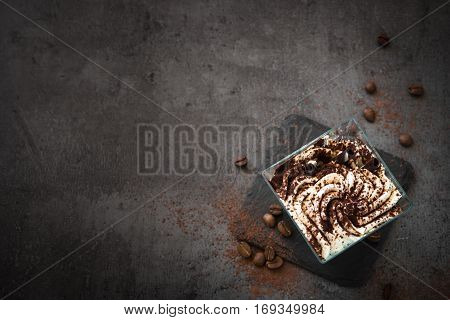 Dessert with whipped cream and chocolate biscuit in a glass. Layered parfait