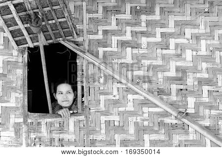 INLE LAKE MYANMAR - JANUARY 12: Portrait of the Burmese woman in traditional make-up looking through the window from the traditional Burmese cottage above Inle Lake on January 12 2011