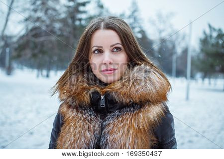 Outdoors winter portrait of beautiful young smiling woman with snowflakes on hair, wearing fur and leather coat