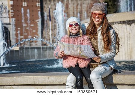 Rediscovering things everybody love in Milan. happy modern mother and daughter travellers in sunglasses near Sforza Castle in Milan Italy with map