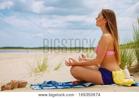 Woman Doing Yoga On Sandy Beach.