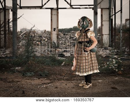 Little girl in a gas mask amidst the ruins. A child in a dress with a broken doll in his hands