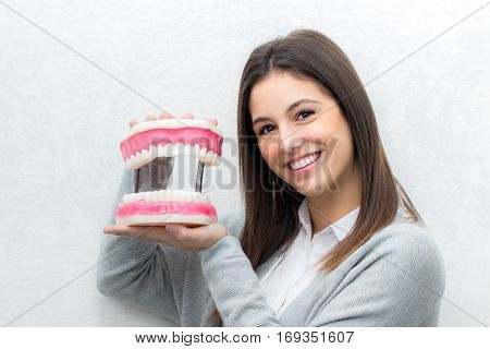 Close up portrait of attractive young girl holding oversize human teeth prosthesis.Cute woman against seamless light background.