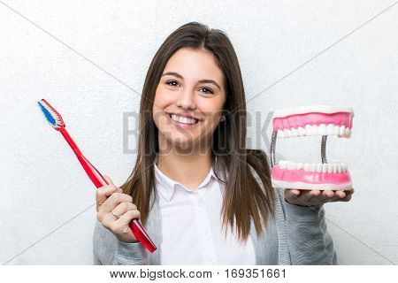 Close up fun portrait of attractive young girl holding oversize toothbrush and human teeth prosthesis.Cute woman standing against light textured background.