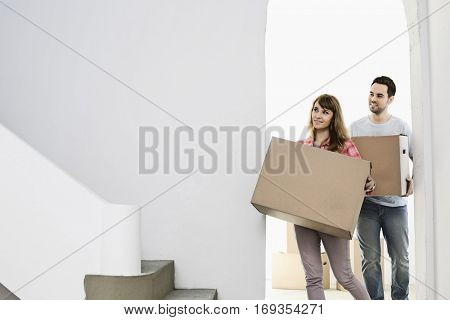 Couple carrying moving boxes