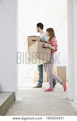 Full-length side view of couple walking with cardboard boxes