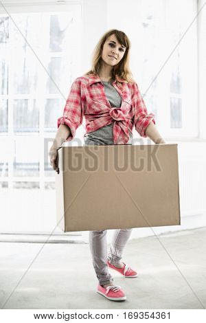 Full-length portrait of woman carrying cardboard box