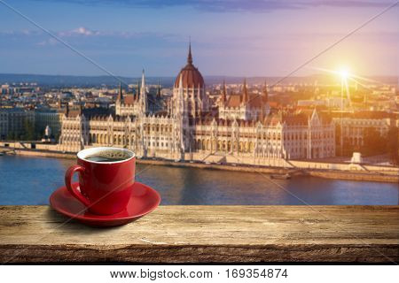 Coffee in cup on wooden table opposite a view of Budapest city