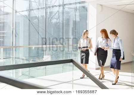 Full-length of businesswomen walking at office hallway