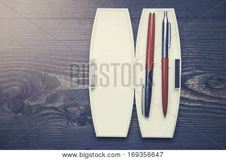 case with fountain pens on wooden table