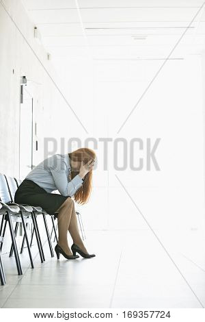 Side view of frustrated businesswoman sitting on chair in office