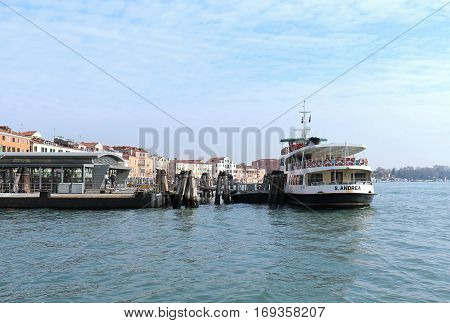 VENICE ITALY - JANUARY 09; One of public boat transport Vaporetto stops with people waiting to board in Venice Italy - January 09 2017: Vaporetto is water bus network with 19 scheduled lines that serve locals and tourists within Venice.