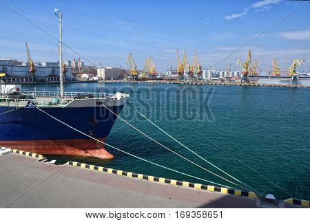 Bow of moored vessel on the pier with seaport cranes and tanks background