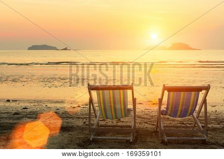 Sun loungers on the sea beach during sunset.