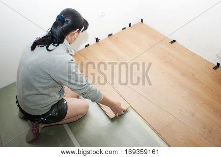 young beautiful woman puting laminate flooring indoor