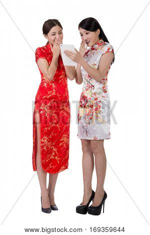 two Chinese women using pad in traditional cheongsam in the new year