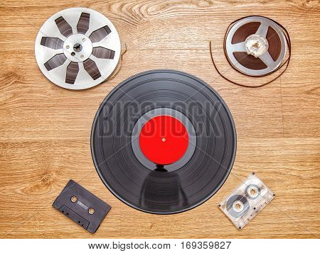 vinyl record with cassetes and reel tape lying onthe floor