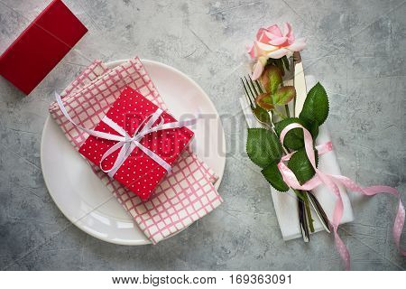 Valentines day table setting. Plate, silverware flower and gift box. Top view copy space.