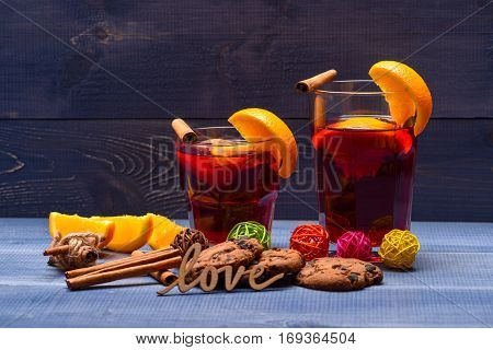 chocolate cookies with wood love text and shot drink of mulled wine or tea with cinnamon spice stick in glass near christmas fir decorative ball orange fruit and pinecone on grey wooden background