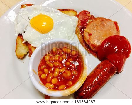 Full cooked English fried breakfast served on a white plate