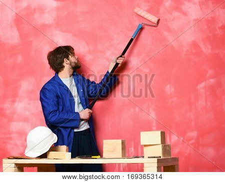 handsome bearded builder man with disheveled hair in blue cloak and building white helmet on table painting wall with long paint roller in studio on pink background copy space