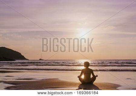 The practice of yoga on the beach at dawn during low tide .Time for peace of mind. Alone with nature. Connection with the universe.