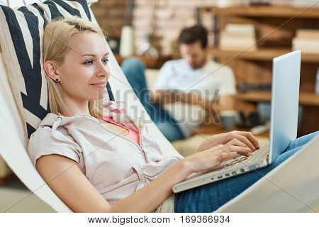 Happy young woman resting in hammock, using laptop computer. Side view.