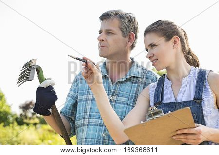 Female supervisor explaining something to gardener at plant nursery