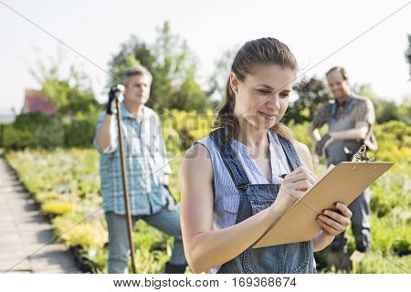 Beautiful supervisor writing on clipboard with gardeners standing in background at plant nursery