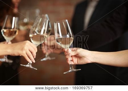 Female hands toasting with glasses of white wine, closeup