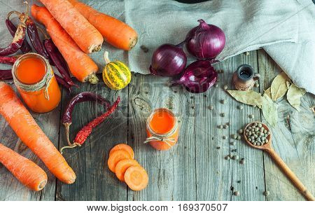 Fresh carrots and carrot juice in a glass container on the gray wooden surface top view