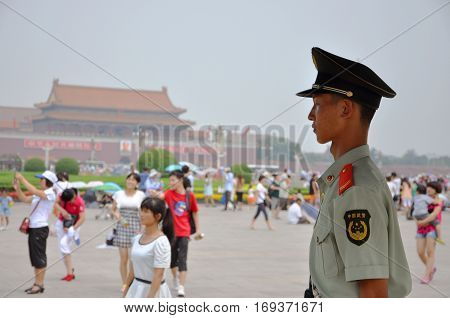 BEIJING, CHINA - JUN.23, 2012: Armed Policeman in the Tiananmen Square, with the Tiananmen Gate in the background, Beijing, China.