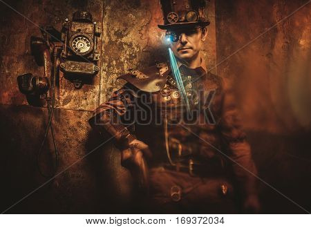 Portrait of steampunk man with various mechanical devices on vintage steampunk background
