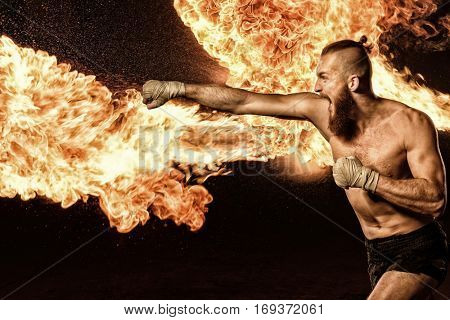 Professional fighter shadowboxing with fire and sparks on background