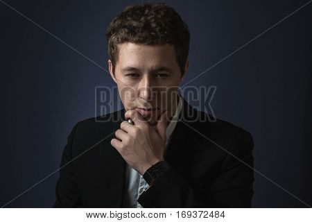 business man in black suit standing brooding