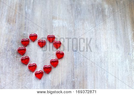Marmalade in the form of hearts laid out in the shape of a large heart on wooden boards.