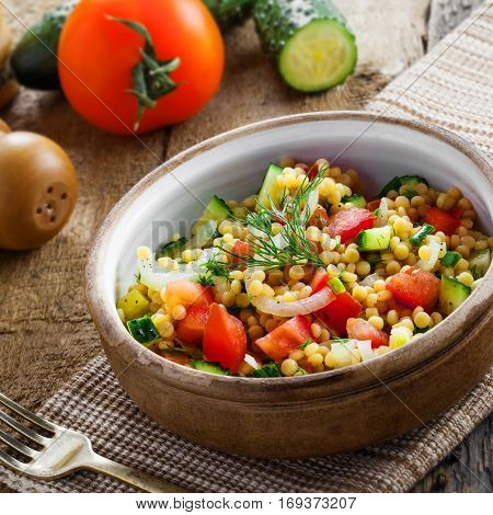Healthy salad for breakfast made of couscous tomatoes cucumber and onion on a table. Traditional Israeli Ptitim meal. Moroccan cuisine food.